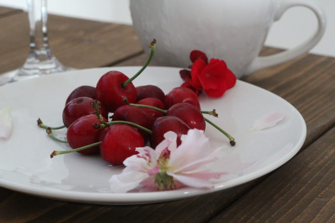 cherries on a plate with a wine glass and coffee cup behind